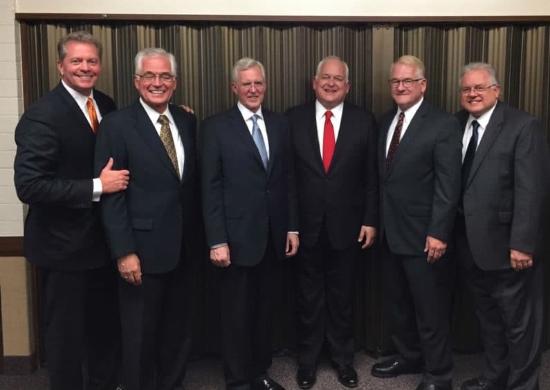 Six smiling men in suits and ties: Todd and Tom Christofferson with four other men including President David Checketts and Bishop Bruce Larson