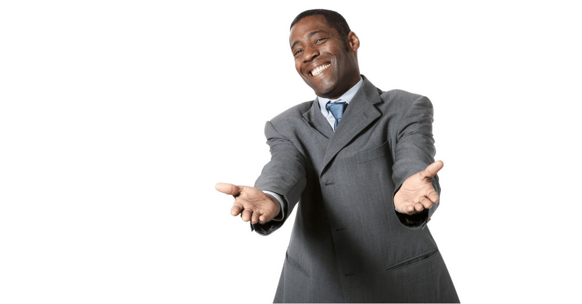 A smiling man in a suit with his arms reached out welcomingly
