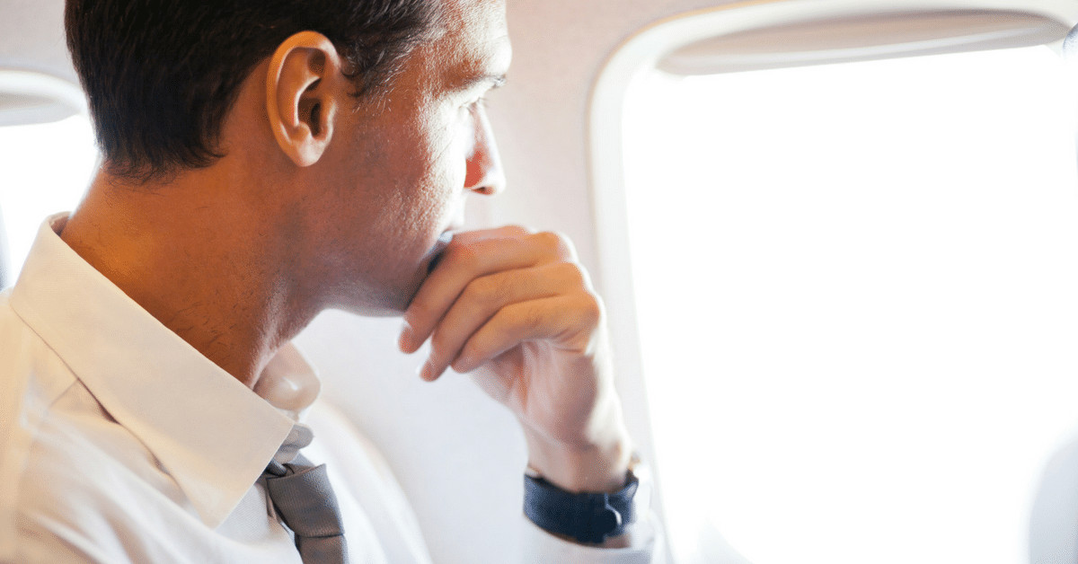 Man in white shirt and tie looking out an airplane window