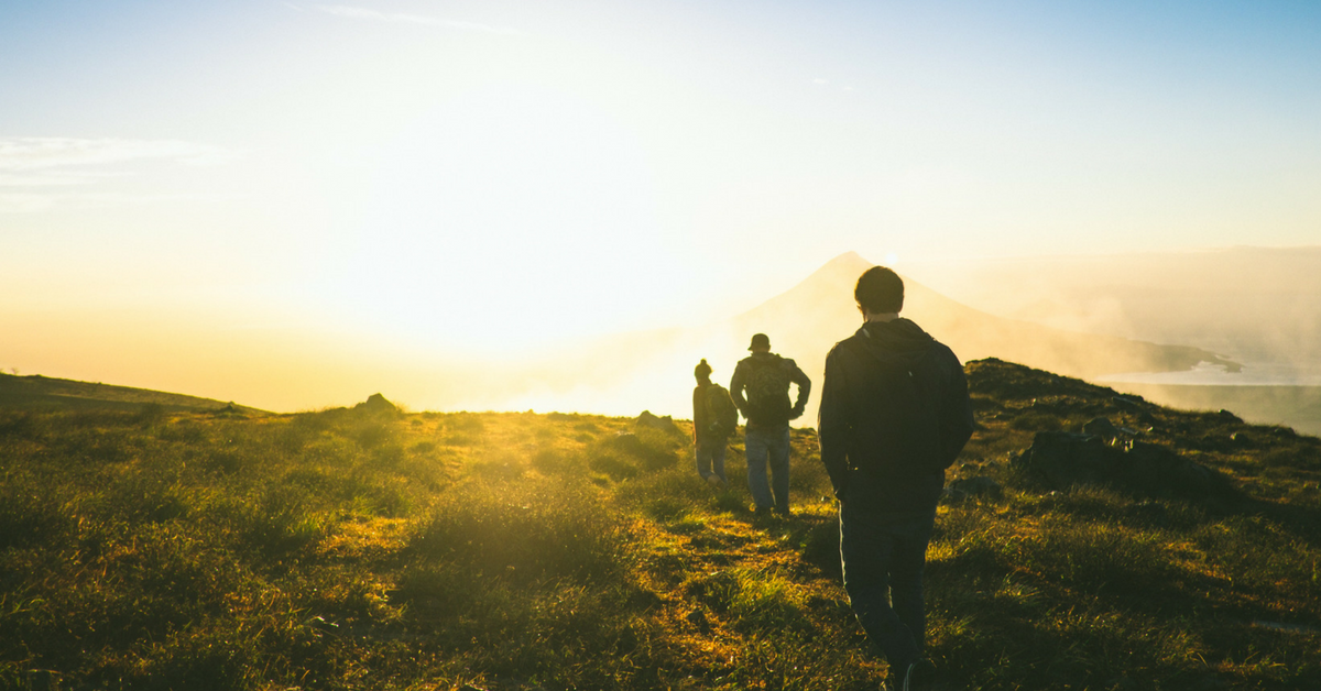 3 people hiking along a path toward the sunlight