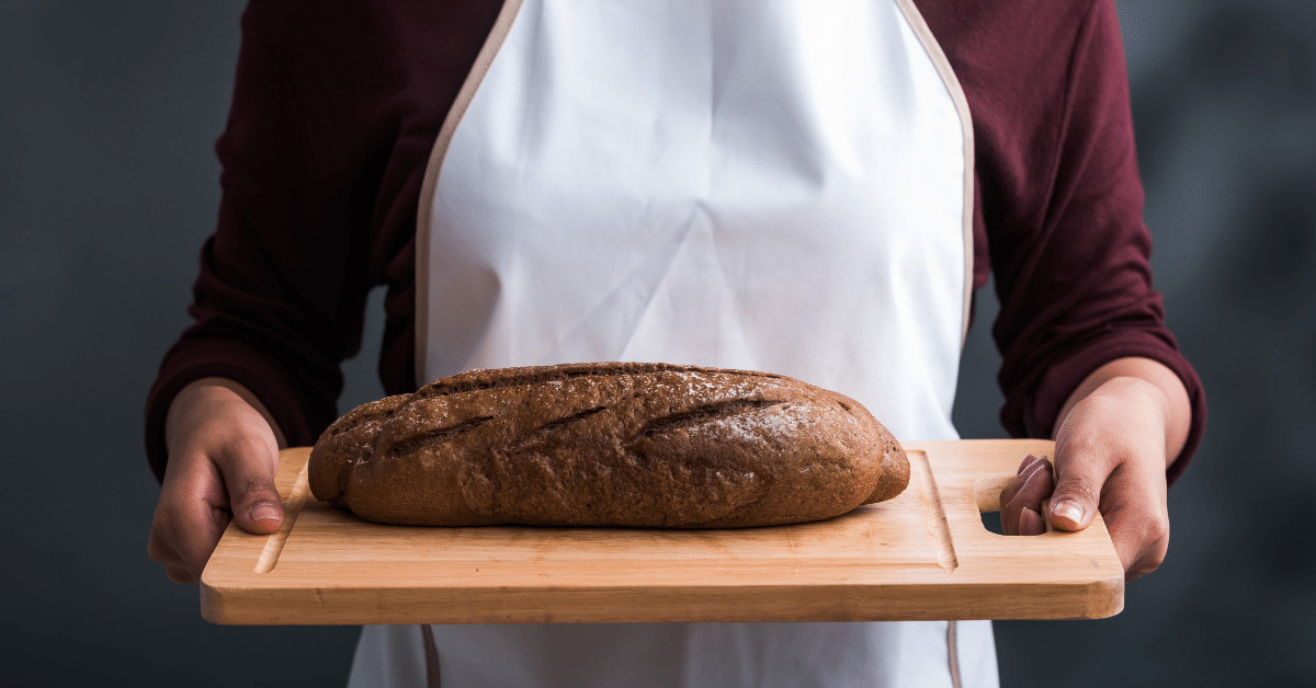 An apron-clad baker offering a loaf of bread on a cutting board