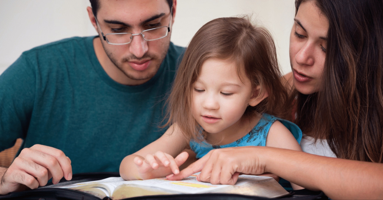 famther, mother, and young child studying the scriptures together at home