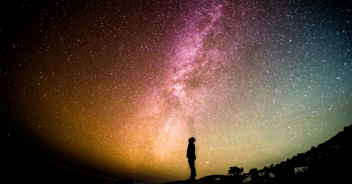 Man standing in the dark, staring up at the colorful Milky Way