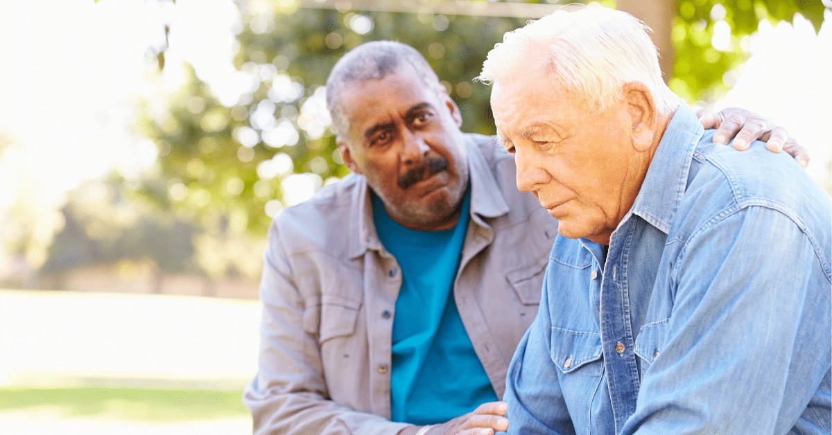 An older man comforts another older man