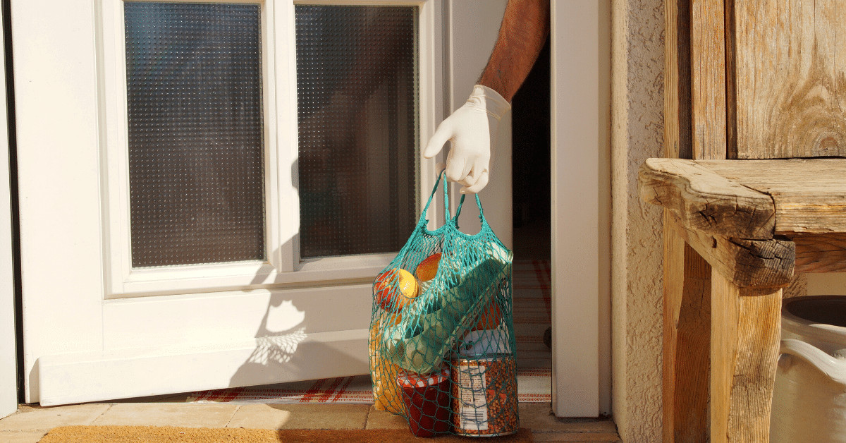 A gloved hand reaching outside a door to pick up a bag of delivered groceries
