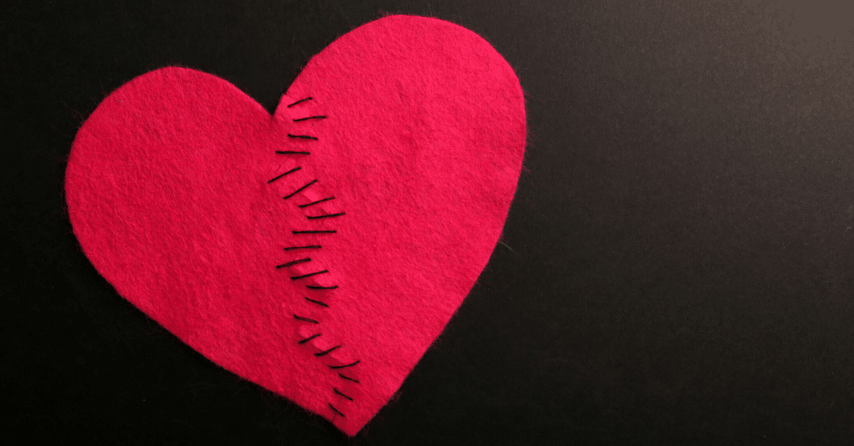 A previously-torn red felt heart, stitched back together