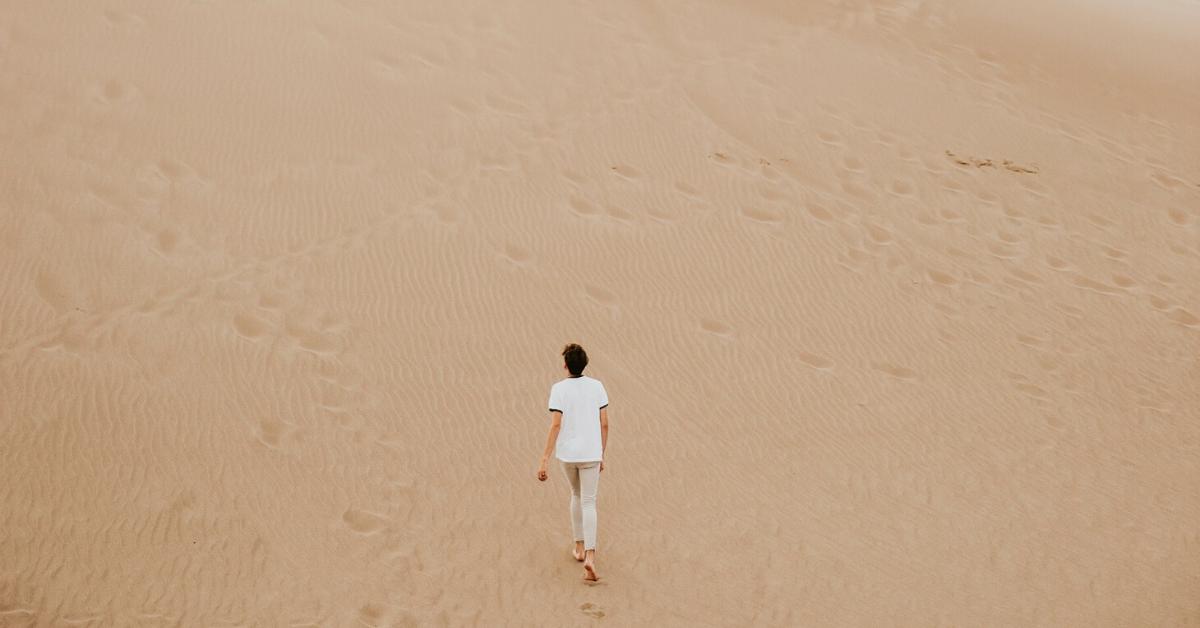 A woman walking alone in a sandy desert landscape