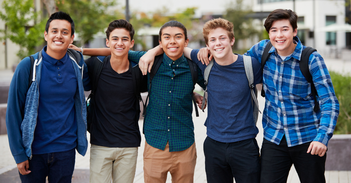 a group of young men, standing together with their arms around each other's shoulders, smiling at the camera
