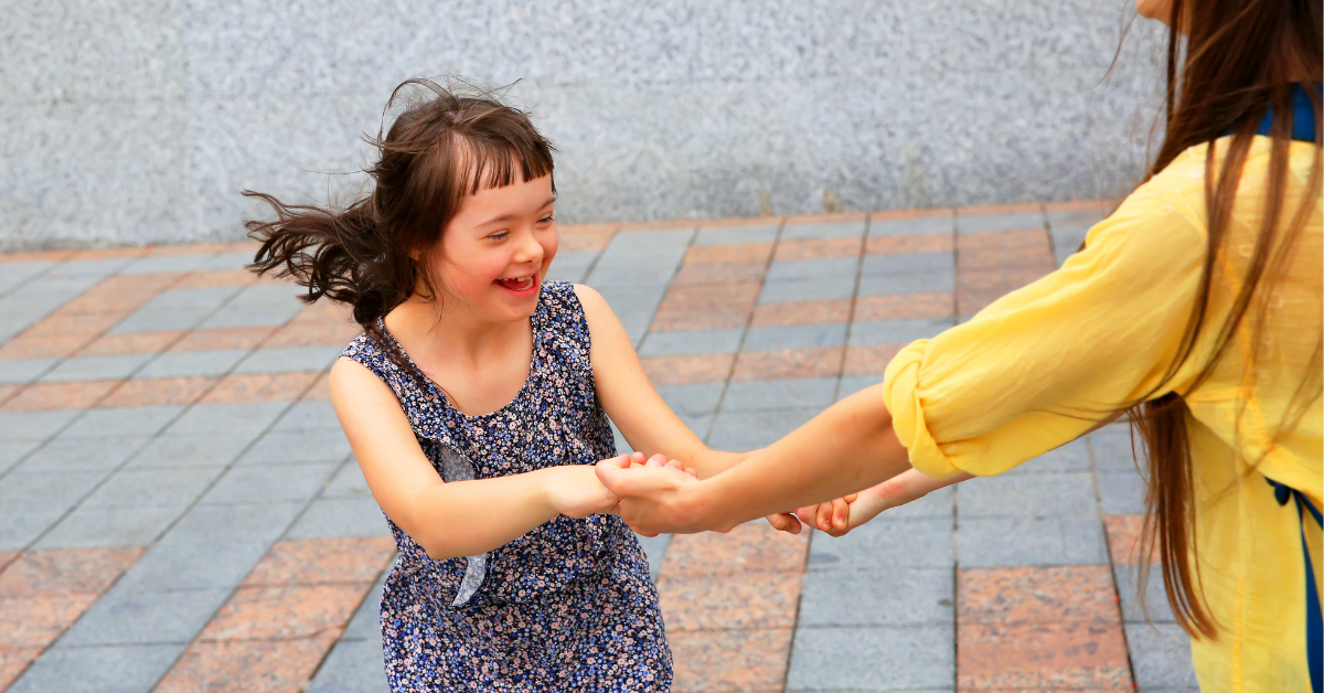 A young special needs girl playing outside with an adult friend