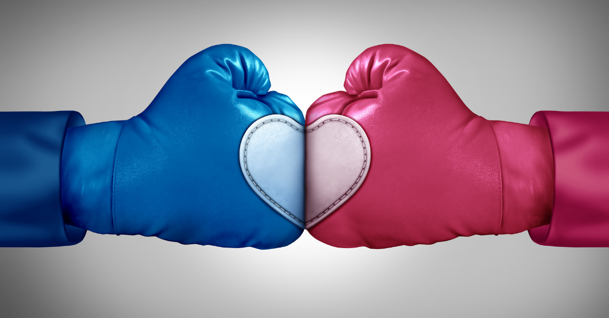Blue and red boxing gloves facing off and forming a heart shape where they meet in the center