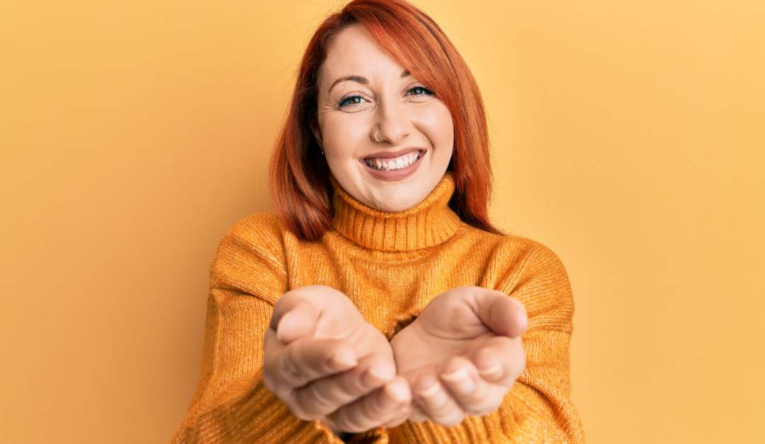 A smiling woman holding out her cupped hands as if making an offering or protecting something