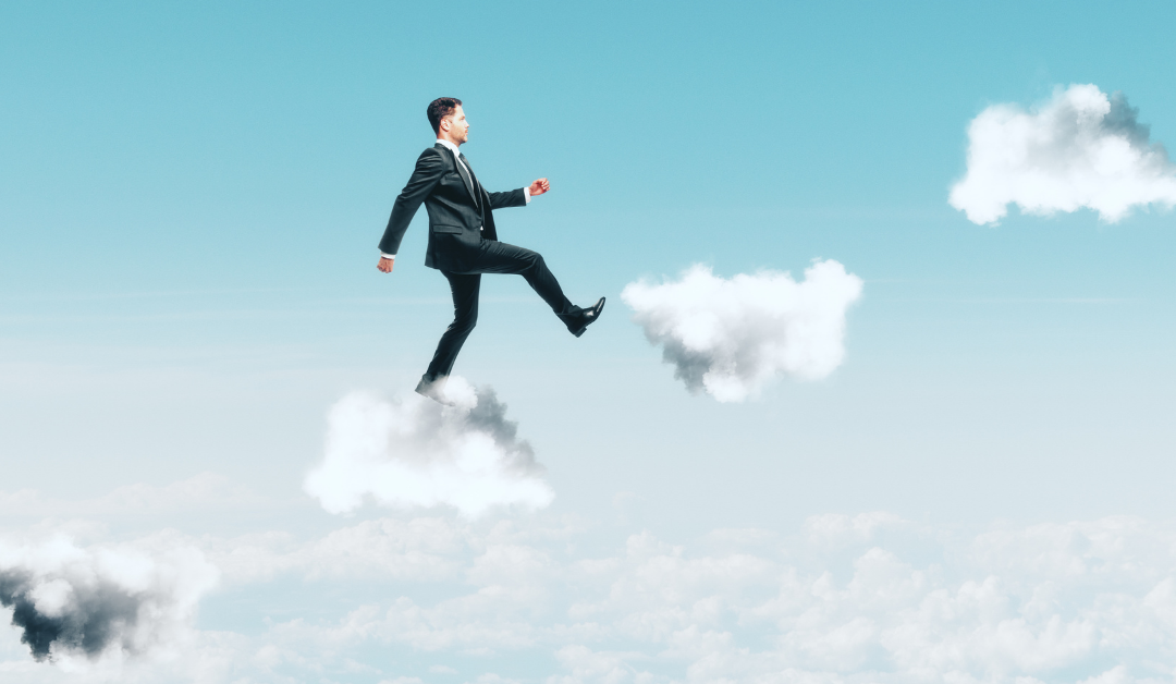 A man in a suit, stepping up a stairway of clouds
