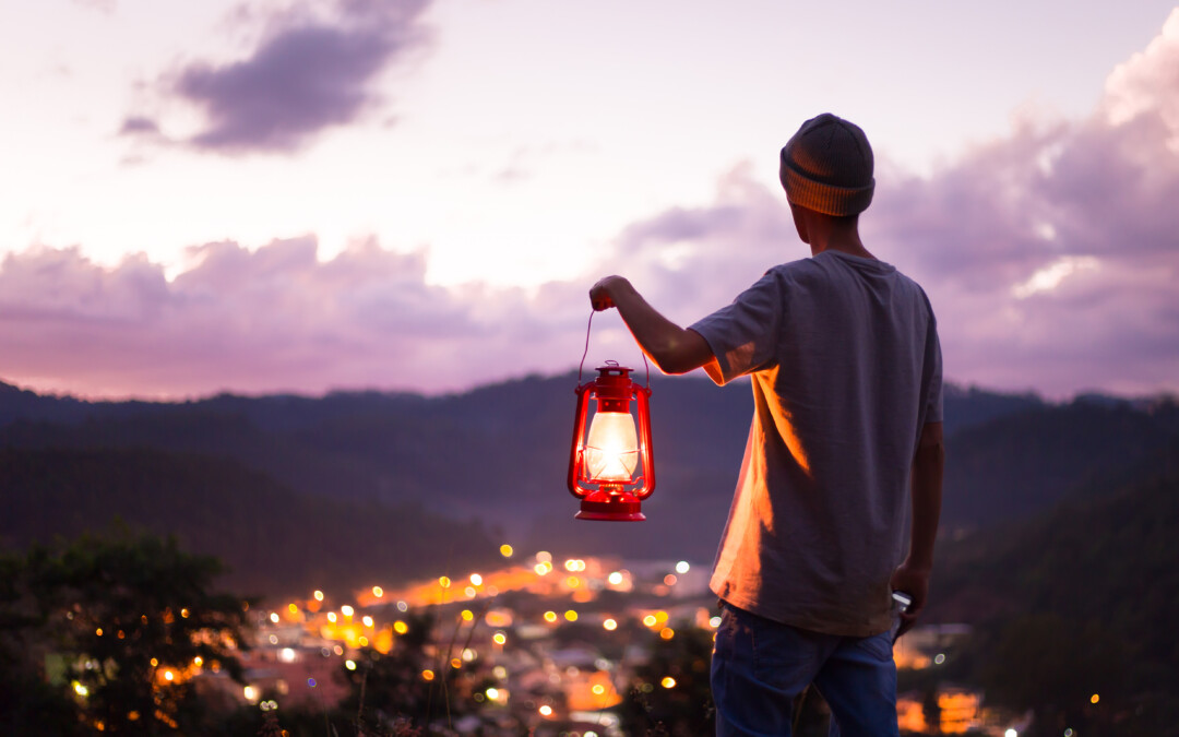A young man standing on a hilltop, holding up a lantern as he looks over a valley with lights in the distance