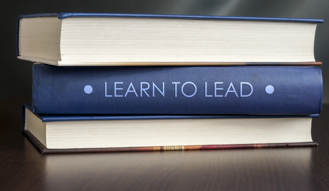 "Books on a table. The title on the spine of one reads ""Learn to Lead""."