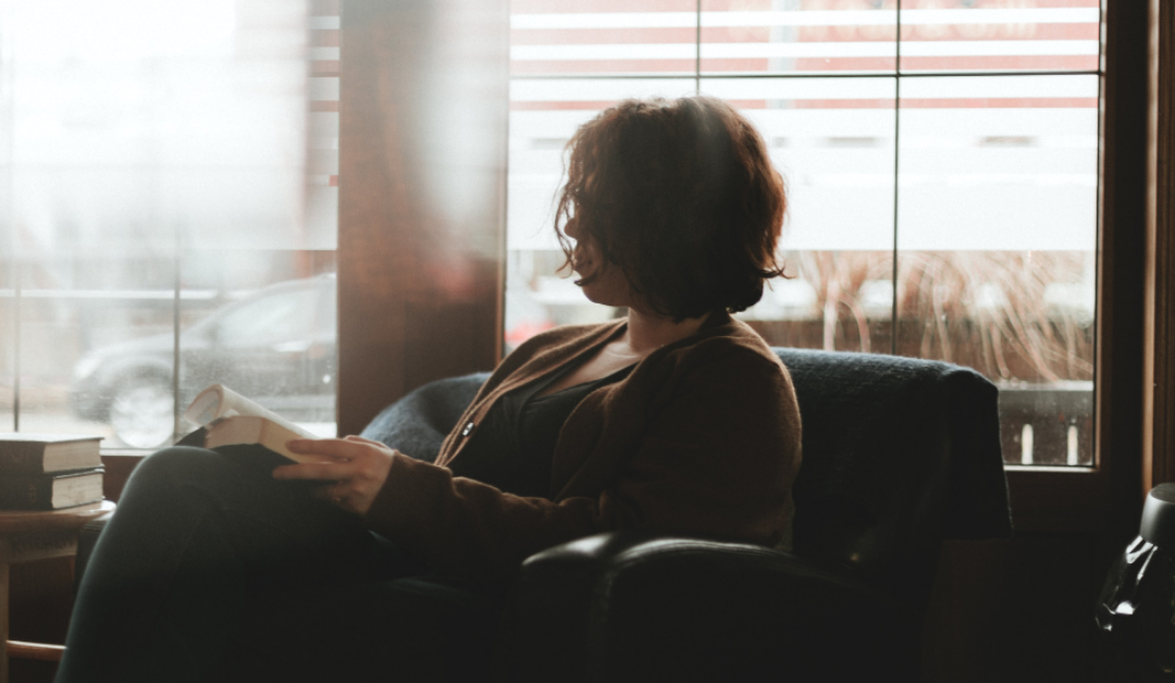 Silhouette of a woman sitting in a chair reading a book next to a bright window