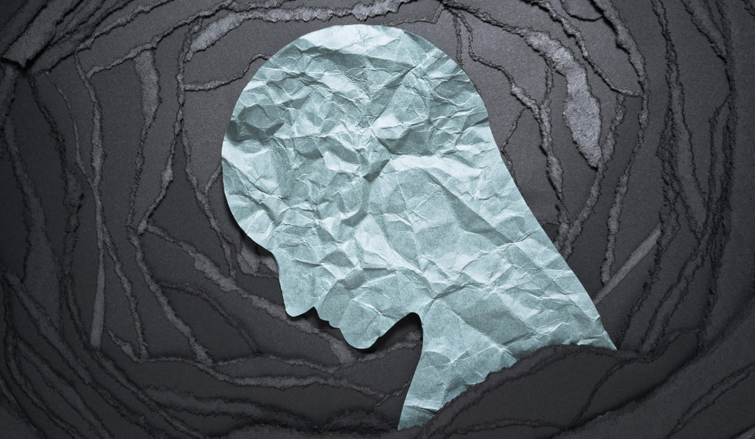 A graphic illustration made with crumpled paper: a bowed head with black waves radiating behind it
